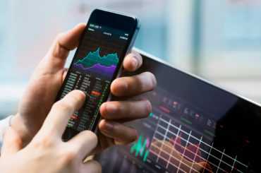 A stock trader trading using a phone and the best stock tips.