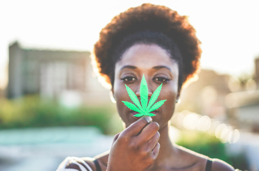 A woman holding a CBD leaf.
